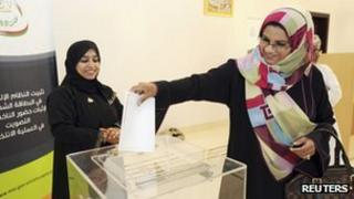 An Omani voting committee member casts her vote early in Muscat