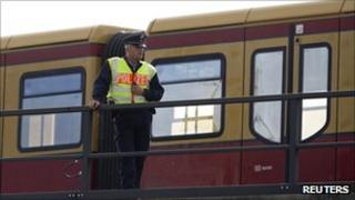 A police officer keeps watch on a rail track in front of a halted S-Bahn commuter train after an incendiary device was found on the tracks in Berlin