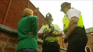 Two police officers stand in the street and speak to a woman