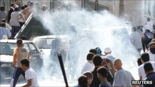 Protesters run for cover after police fired tear gas in Tunis. Photo: 14 October 2011