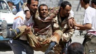 A wounded dissident soldier is carried for treatment in Sanaa, 15 Oct