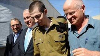 freed Israeli soldier Gilad Shalit (2nd R) walks with (L-R) Defence Minister Ehud Barak, Israeli Prime Minister Benjamin Netanyahu his father Naom Shalit at Tel Nof Airbase on October 18, 2011 in central Israel.