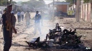 A Somali government soldiers secure the scene of a suicide attack that killed at least five people on 18 October 2011 in Mogadishu