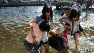 Women carrying children through flood water in a suburb of Bangkok