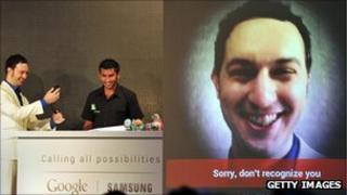 Two men demonstrating the facial recognition feature of the Samsung Galaxy Nexus mobile