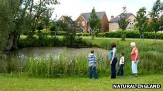 People standing in front of pond, Cambourne