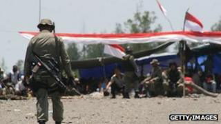 Armed Indonesian troops guard striking workers manning a road block inside the Freeport McMoran complex in Timika