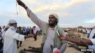 An al-Shabab spokesman addresses the media next to what they say are the bodies of 76 Burundian peacekeepers from the African Union Mission to Somalia killed during heavy fighting in Dayniile district, south of Mogadishu October 20, 2011.