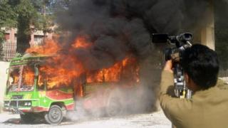 Pakistani media film a bullet-riddled burning bus in Quetta on October 4, 2011.