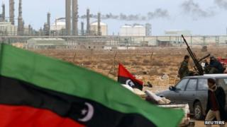 The Kingdom of Libya flag flies in front of a refinery in Ras Lanuf in this 8 March 2011