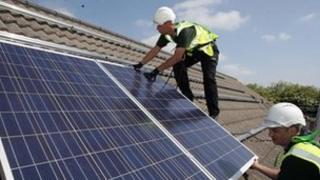 Workmen installing solar panels on to the roofs of homes in Delabole near Bodmin