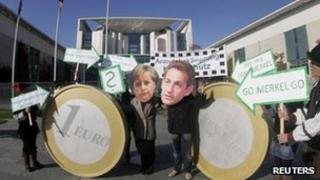Protesters wearing masks of Angela Merkel (left) and Nicolas Sarkozy demonstrate outside German government offices with mock giant euro coins, 21 October