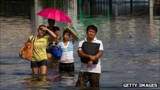 Thai residents make their way through the flooded streets October 21, 2011 in Pathumthani on the outskirts of Bangkok
