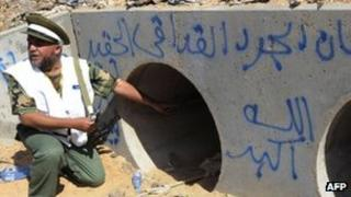 An NTC fighter points to a drainage pipe in which Col Muammar Gaddafi is said to have been captured, Sirte, 20 October 2011
