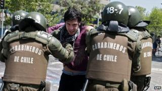 Chilean police arrest a demonstrator during protests on 19 October