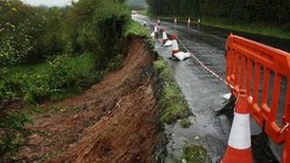Flooded road collapses