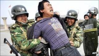 Chinese police make a mock arrest during a drill rehearsing how to control demonstrations in Urumqi, in far-western Xinjiang province, on 1 April 2011