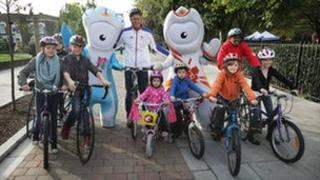 Five-time Olympic swimmer Mark Foster with children and London 2012 Mascots Wenlock and Mandeville on an enhanced cycle scheme in Hackney, London, pic courtesy of ODA