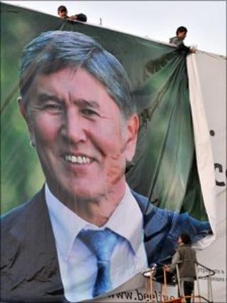 men hang Almazbek Atambayev campaign poster