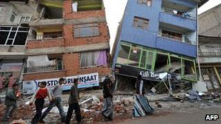 People walk in front of collapsed buildings in Ercis after the earthquake in Turkey Pic AFP
