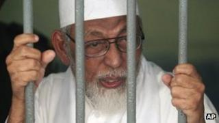 Radical cleric Abu Bakar Ba'asyir talks to reporters from behind bars of a holding cell at a district court in Jakarta, Indonesia, on 9 May 2011