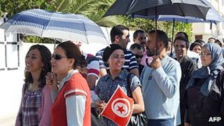 Tunisians wait to vote outside a polling station