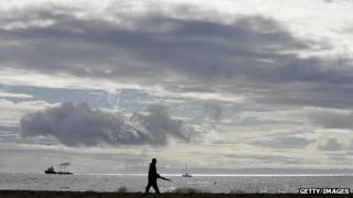 A man walks along a bay with storm clouds in the background.