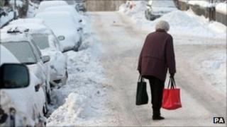 Elderly woman walking through the snow in Peebles last winter