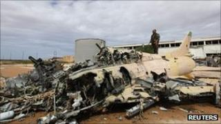 A military aircraft of Muammar Gaddafi's air force lies destroyed after a Nato strike in Sirte, 6 October 2011