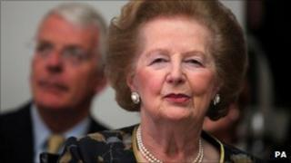 Margaret Thatcher, with John Major in the background