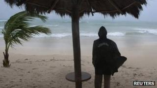 A security guard looks at the sea during a rain caused by Rina in Playa del Carmen. Photo: 27 October 201