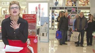 Welsh National Opera performer Anne Williams-King shows her anguish at the cosmetics counter in Debenhams as shoppers watch