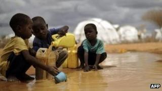 This file picture taken on 16 October 2011, shows Somali boys fetching water from a puddle that formed after rain at the IFO-2 complex in the sprawling Dadaab refugee complex in Kenya