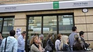 People queue outside an employment office in Seville, Spain