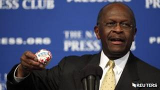 Republican candidate Herman Cain holds a cupcake that says 9-9-9 at the National Press Club on 31 October 2011