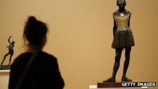 A woman looks at Degas' La Petite Danseuse de Quatorze Ans