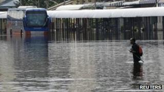 Man wading through flooded station in Bangkok