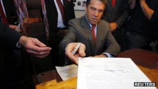 Rick Perry hands in his documentation for the New Hampshire primary 28 October 2011
