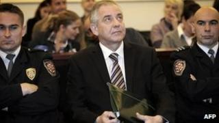 Former Croatian Prime Minister Ivo Sanader, flanked by court police