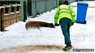Worker spreads grit in residential area - generic image