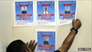 A man puts up wanted posters for four Honduran policemen accused of killing two students