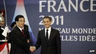 French President Nicolas Sarkozy (R) shakes hands with Chinese President Hu Jintao prior to their talks in Cannes, 2 November 2011