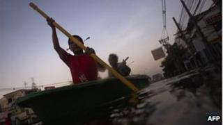 A boy and man row their boat through a flooded neighbourhood in Bangkok November 3