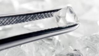 Rough diamond held between tweezers