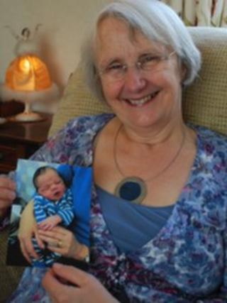 Grandmother holding a photograph of her grandson