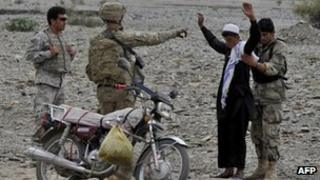 US soldier and Afghan soldier search a boy 5 October 2011