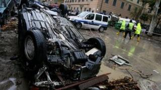 People walk past part of cars and debris in a street of Genoa after heavy rainfall on 5 November 2011