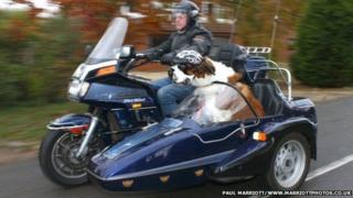 Alan Valkeith riding motorbike with Harley, a St Bernard dog, beside him