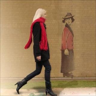 Woman walking past Lowry type figure on wall