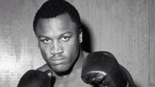 Joe Frazier posing in boxing gloves